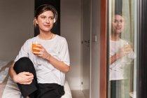 Contenida joven hembra en ropa casual sonriendo y bebiendo jugo fresco sentada en la cómoda cama cerca de la ventana - foto de stock