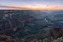 Dall'alto del pittoresco paesaggio di formazioni rocciose grezze e fiume situato nel Grand Canyon National Park in Arizona negli Stati Uniti sotto il cielo colorato all'alba — Foto stock