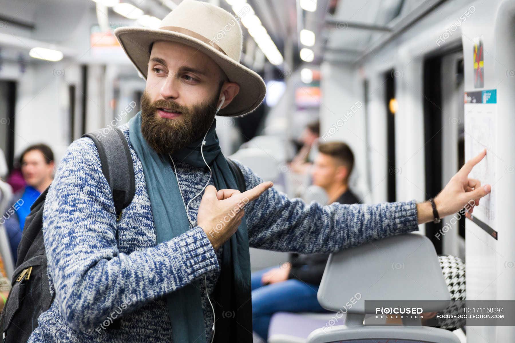 Man Looking At Subway Map.Tourist In Wagon Pointing At Subway Map And Looking Away With