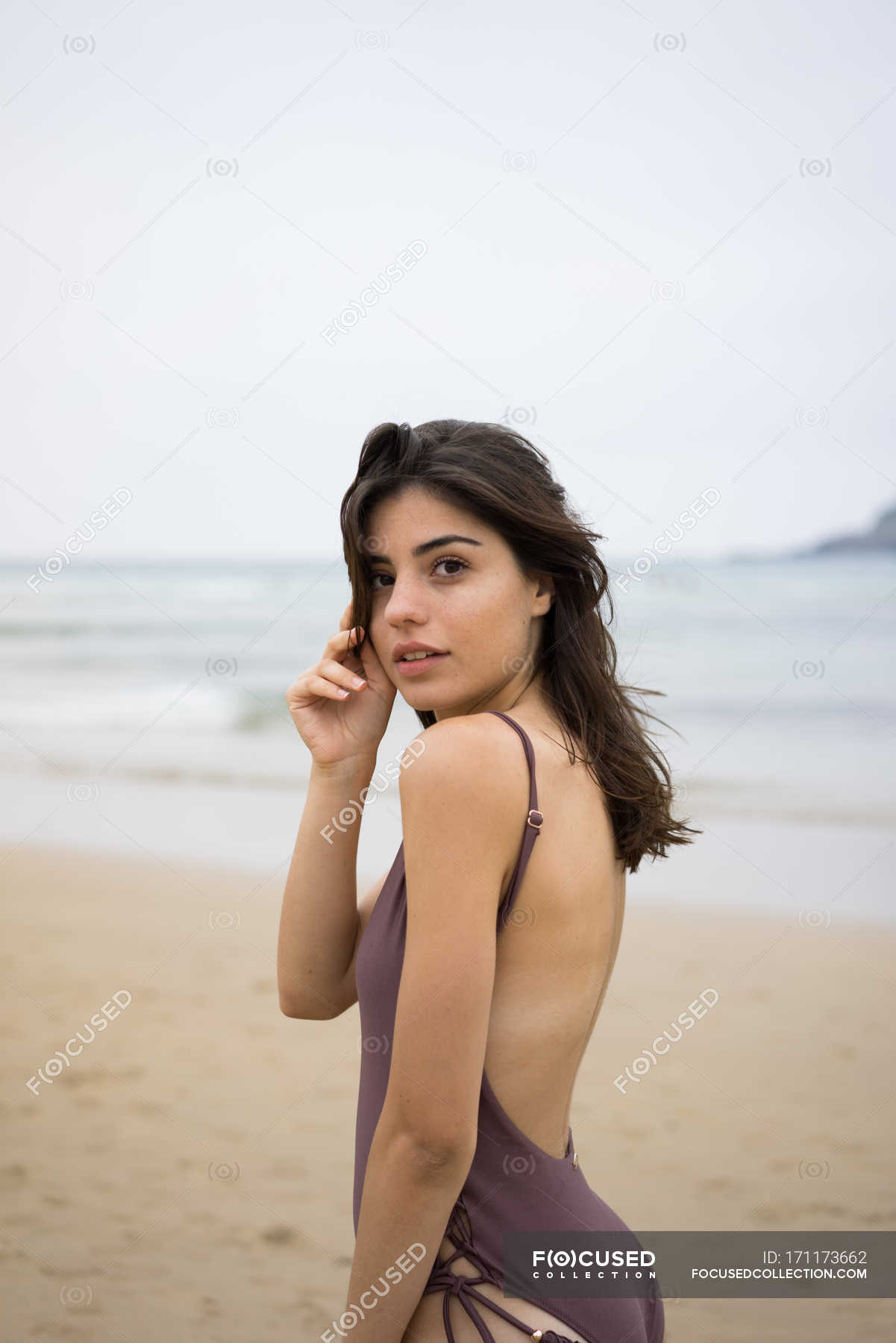 Brunette girl photo Brunette Girl In Swimsuit Posing On Beach And Looking Over Shoulder At Camera Tranquil Tropical Stock Photo 171173662