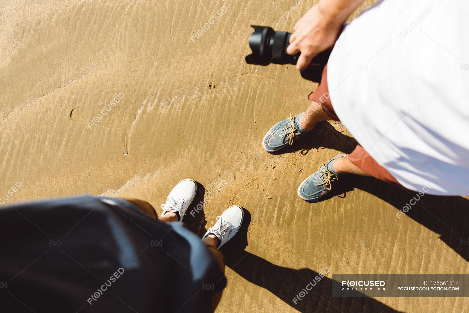 Looking Down View Of Two Persons Standing On Wet Sand With Stock Photos
