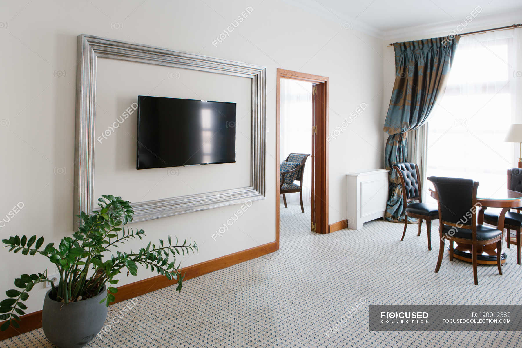 Interior Of Luxury Hotel Room With Chairs And Tv Set Hanging On Wall Stock Photos