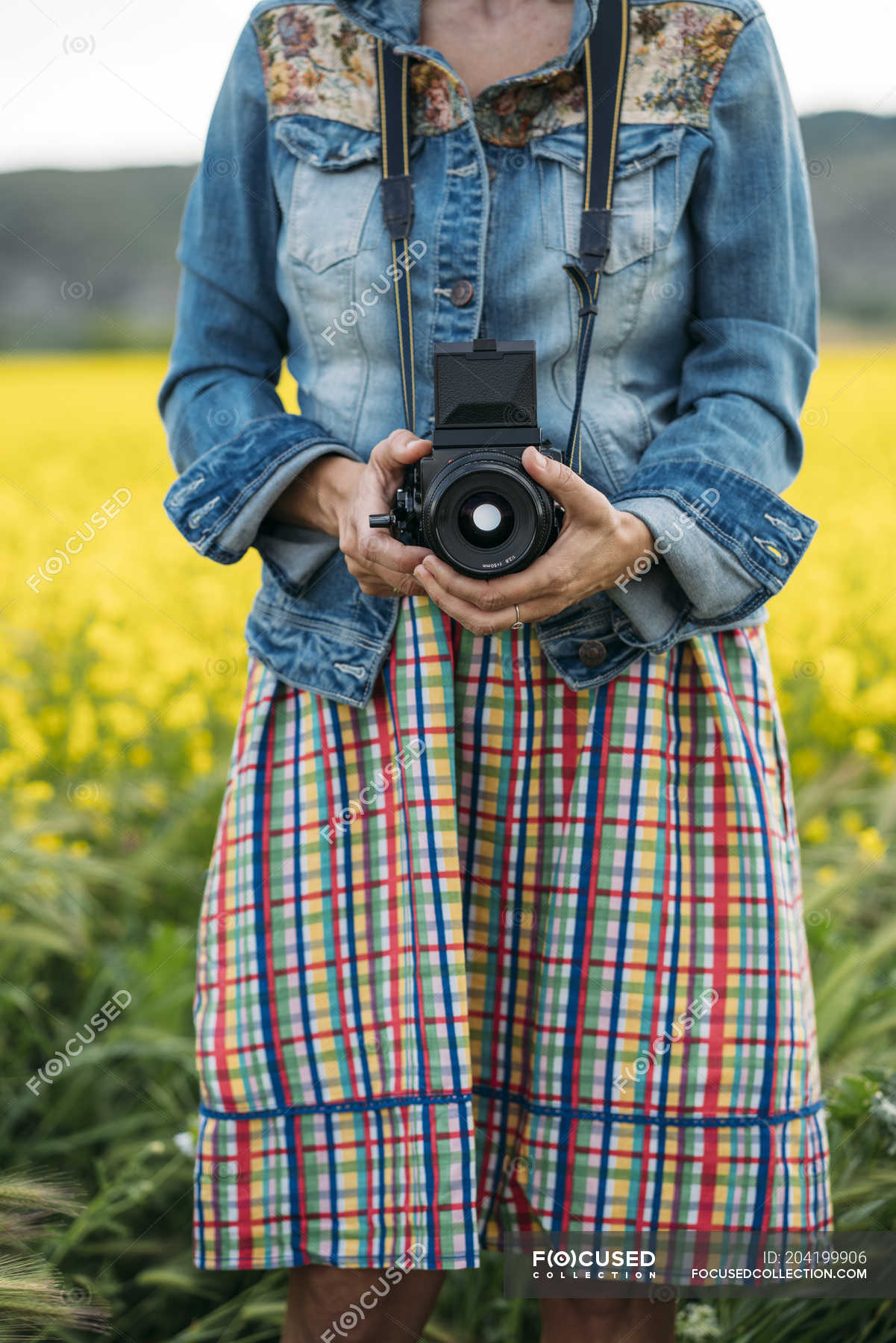 3e6be25b9d9 Woman in colored dress and denim jacket holding photo device in nature —  Stock photos