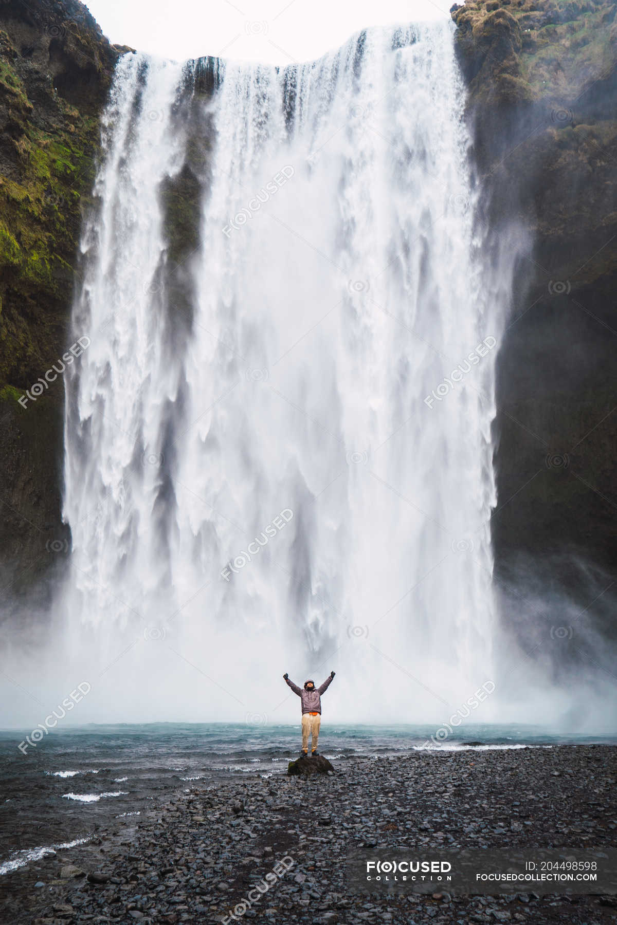 Excited Man With Arms Up Standing In Front Of Waterfall Splashing Warm Clothes Stock Photo 204498598