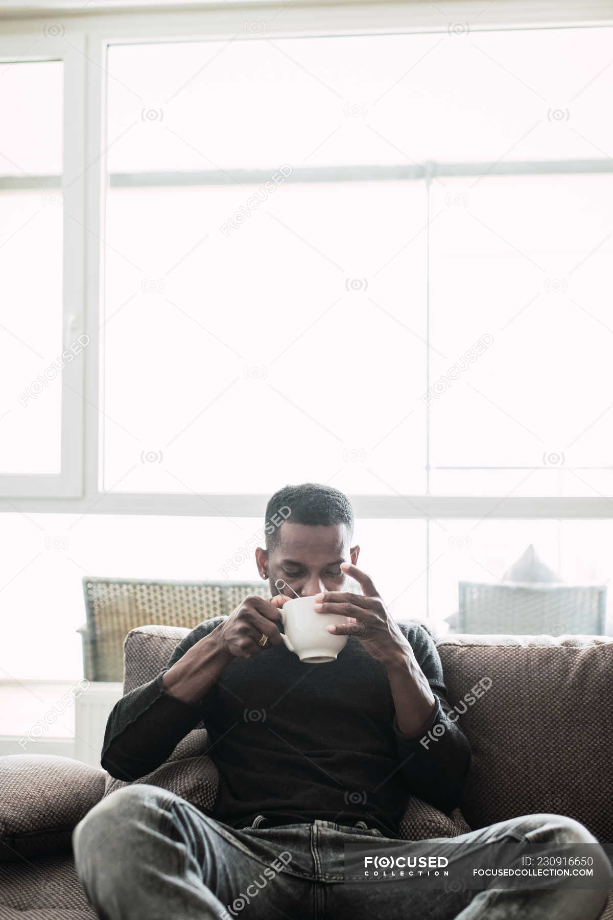 Pensive Black Man Relaxing On Sofa With