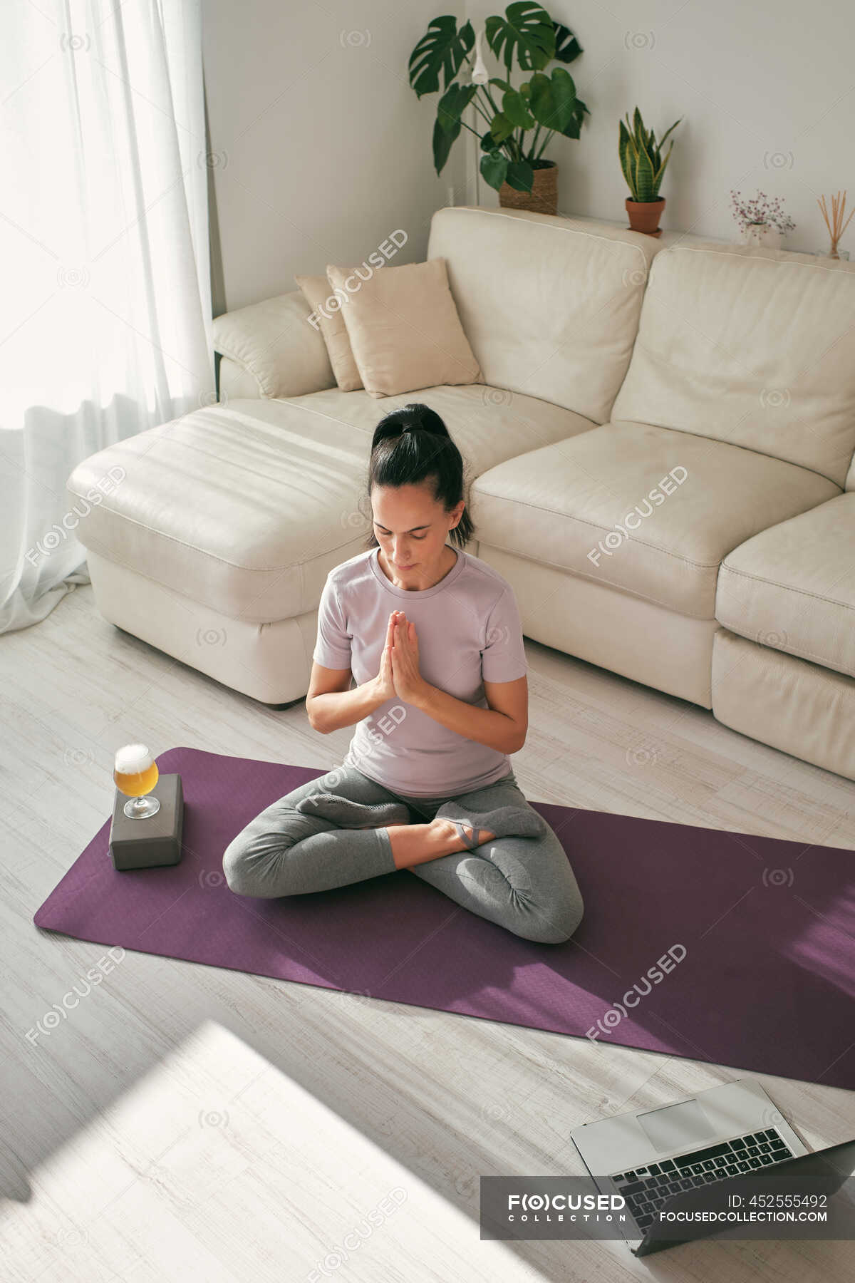 From above of tranquil female sitting in Lotus pose on mat with ...