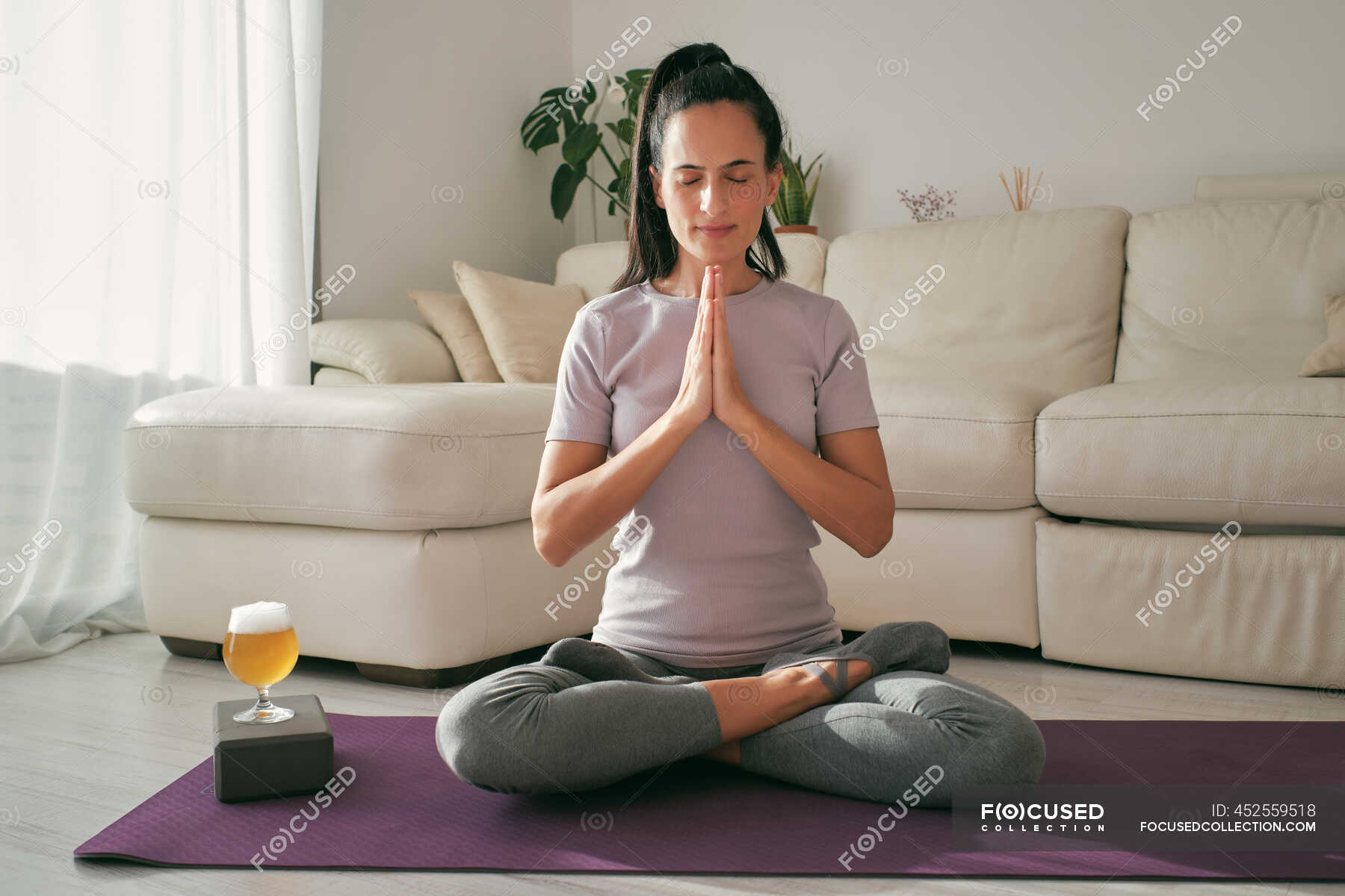 Tranquil female sitting in Lotus pose on mat with glass of beer and ...