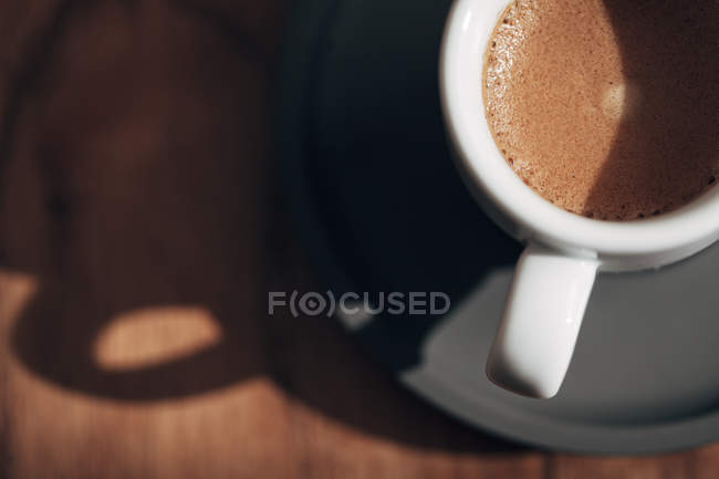 White cup of coffee on dark saucer — Stock Photo