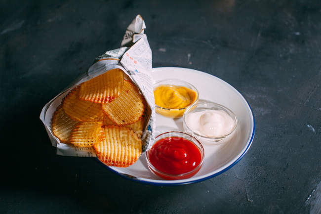 Potato chips with different sauces — Stock Photo