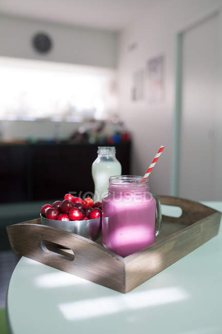 Smoothie with cherries on wooden tray — Stock Photo