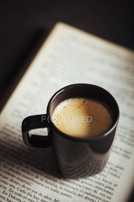 Cup of coffee on opened book — Stock Photo