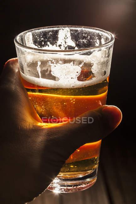 Скло світле пиво в людської руки. — стокове фото