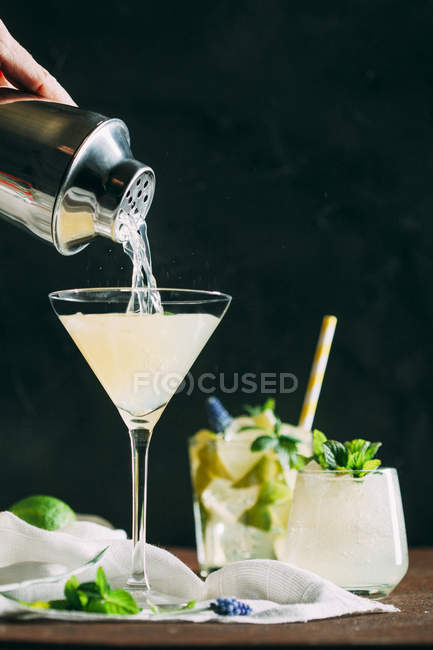 Hand pouring cocktail into glass — Stockfoto