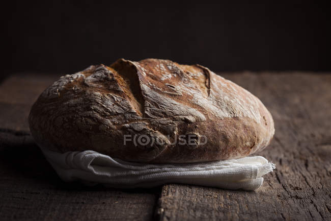 Loaf of bread on white cloth — Stock Photo