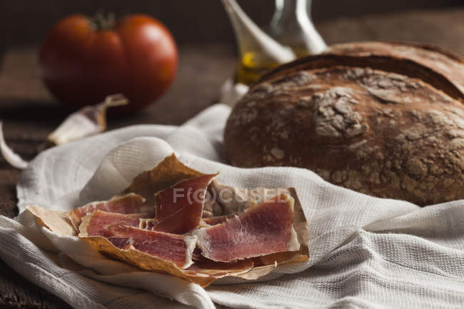 Bread and prosciutto on wooden table — Stock Photo