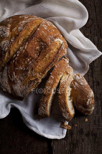 Loaf of sliced bread on white cloth — Stock Photo