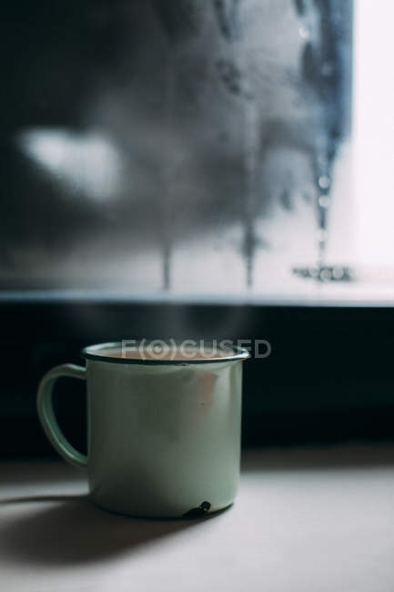 Cup of coffee on windowsill — Stock Photo
