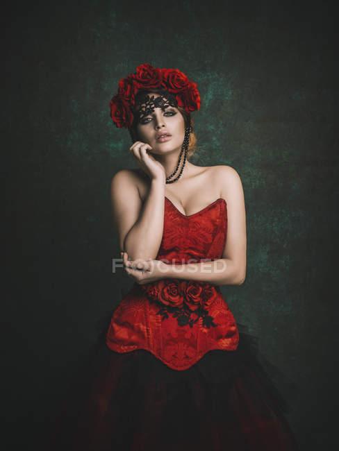 Femme sensuelle en fleurs rouges et robe — Photo de stock