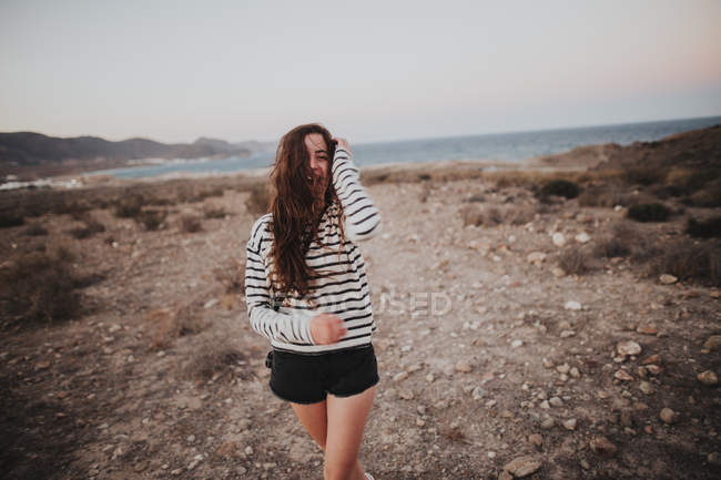 Brunette woman walking against of seascape — Stock Photo