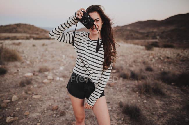 Життєрадісна дівчина брюнетка з цифрової камери — стокове фото
