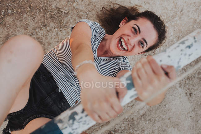 Cheerful girl hanging on wooden bar — Stock Photo