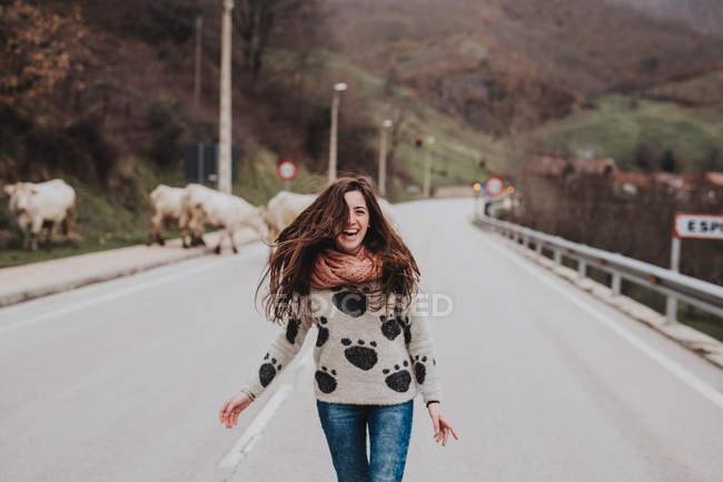Jeune fille gaie sur route asphaltée — Photo de stock