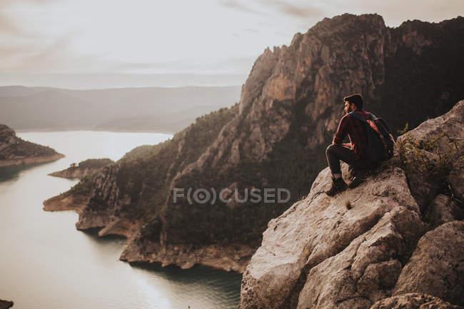 Joven viajero sentado en roca - foto de stock