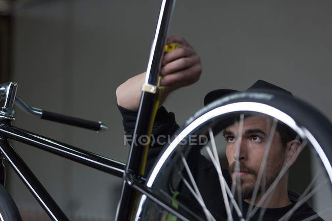 Craftsman taking measurements of bicycle — Stock Photo