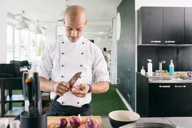 Koch in einheitlichen schneiden Zwiebel — Stockfoto