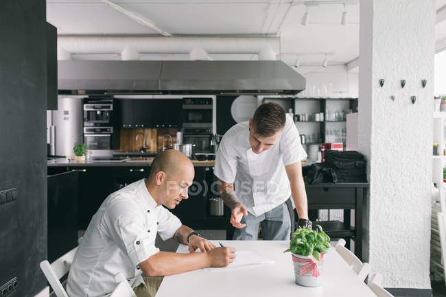 Cuisinier professionnel, prendre des notes pour les étudiants — Photo de stock