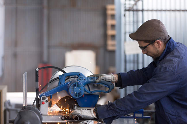 Man working on saw machine — Stock Photo