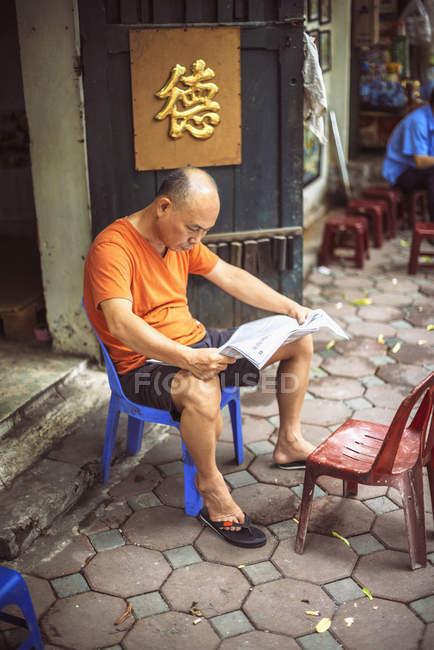 В'єтнамська-людина, читаючи газету на вулиці — стокове фото