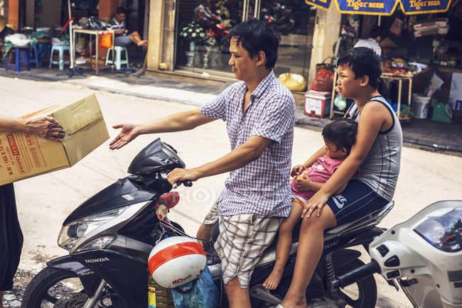 Homme conduite famille par moto — Photo de stock