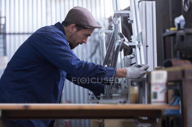 Arbeiter schaut sich eiserne Details an — Stockfoto