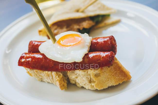 Huevo frito con salchichas sobre pan - foto de stock