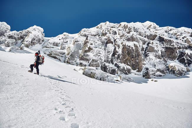 Homme randonnée dans les montagnes enneigées — Photo de stock
