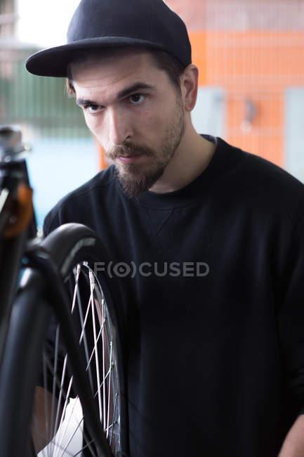 Чоловік дивиться на колесо велосипеда — стокове фото