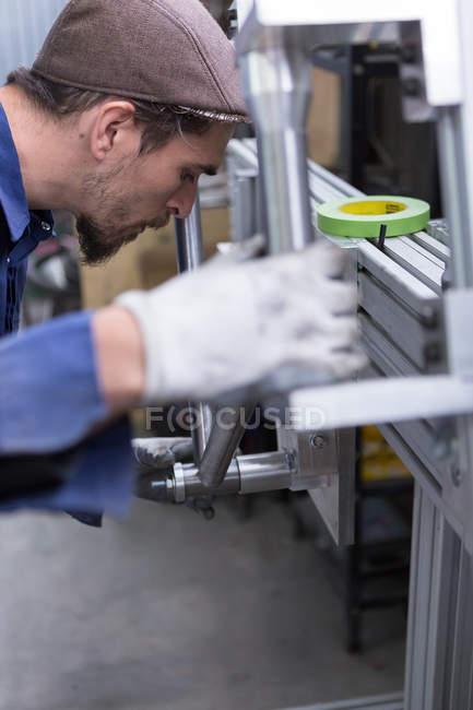 Man looking at metal details — Stock Photo
