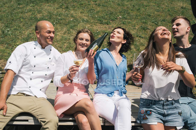 Friends with champagne sitting outdoor — Stock Photo