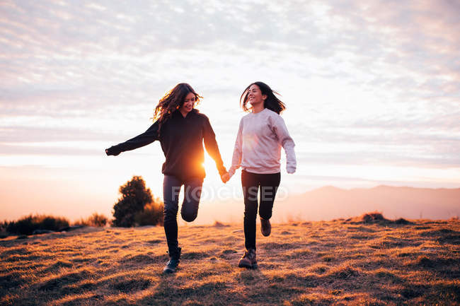 Girls holding hands and running in mountains — Stock Photo