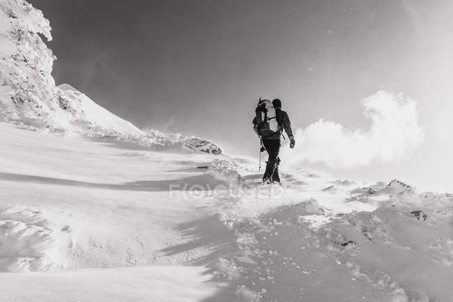 Hombre trekking en montaña nevada - foto de stock