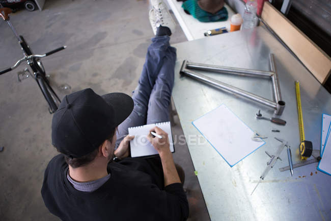 Craftsman writing measurements in notebook — Stock Photo