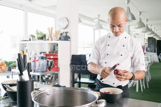 Chef cutting onion in kitchen — Stock Photo