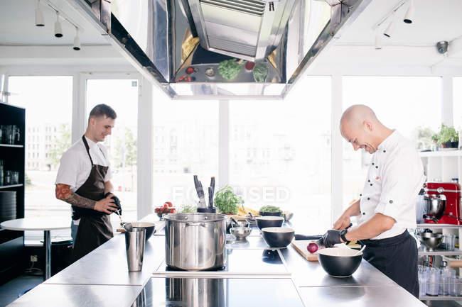Chef e estudante cozinhando na cozinha — Fotografia de Stock