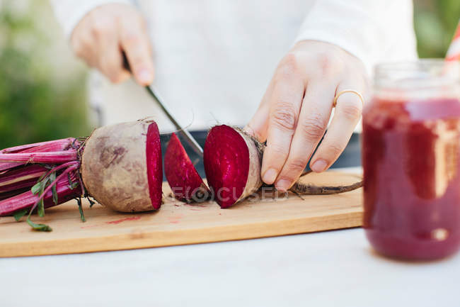 Female hands cutting fresh beet — Stock Photo