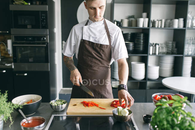 Man in apron cutting vegetables — Stock Photo