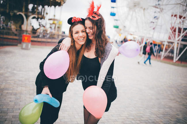 Smiling girls in masks holding balloons — Stock Photo
