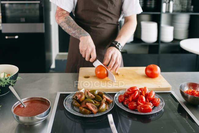 Cozinhar em tomates de corte avental — Fotografia de Stock