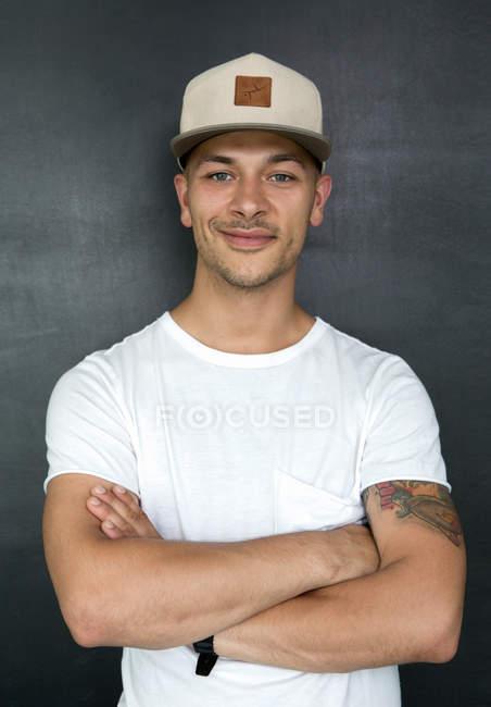 Jeune homme élégant en casquette blanche — Photo de stock