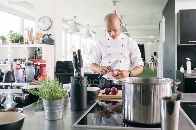 Chef cortando cebollas en la cocina - foto de stock